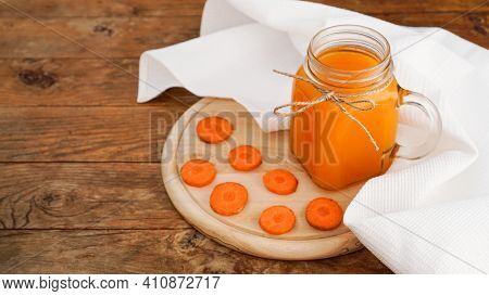 Bright Orange Carrot Juice In A Glass Jar On A Wooden Background. Juice And Chopped Carrots. Homemad