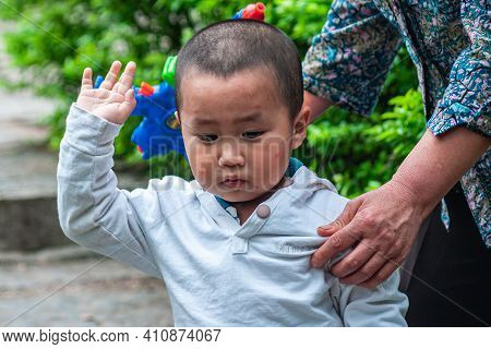 Guilin, China - May 11, 2010: Seven Star Park. Little Boy In White Shirt Salutes With Faded Green Fo