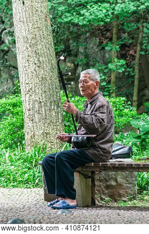 Guilin, China - May 11, 2010: Seven Star Park. Man Sitting On Bench Plays The Erhu Or Chinese Violin