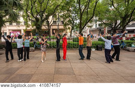 Guilin, China - May 11, 2010: Mostly Women Dance For Fitness On Brown Stone Square Under Green Trees