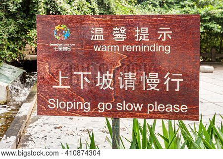 Guilin, China - May 11, 2010: Seven Star Park. White On Red Wood Warning Sign Asking To Go Slow On A