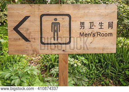 Guilin, China - May 11, 2010: Seven Star Park. Sign Pointing To Men Toilet With Black Script On Beig
