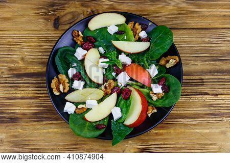 Autumn Spinach Salad With Apple, Feta Cheese, Walnut And Dried Cranberry On Wooden Table. Top View.