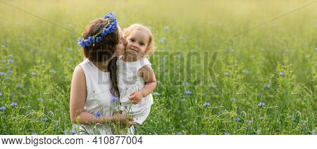 Mother And Daughter In A Field Of Cornflowers At Sunset. The Mother's Care And Love For The Child. L