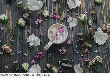 Coffee With Lilac Petals Flat Lay On Dark Wooden Background With Space For Text. Fresh Aromatic Coff