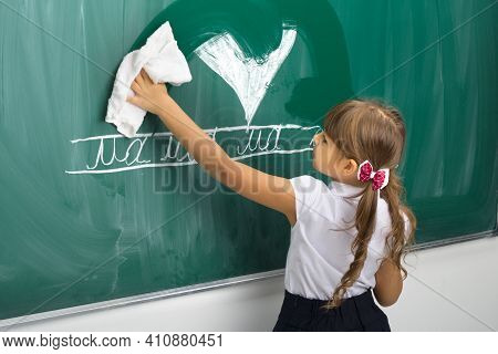 Schoogirl Wiping Chalkboard With Rag. View From Behind Of Cute Elementary School Student Girl Standi