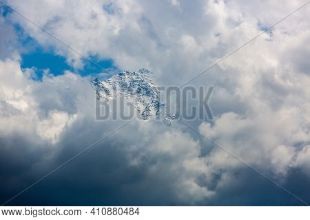 Caucasian Peak Close-up. Dramatic Clouds And Blue Skies. Snow Covered Peak. The Summit Of The Mounta