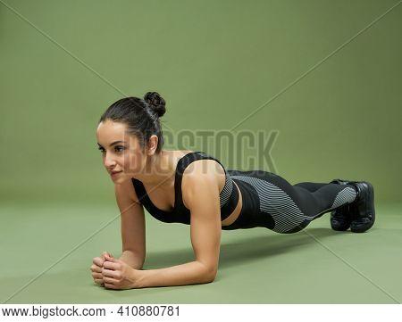 Beautiful Young Woman In Sportswear Doing Plank In Studio
