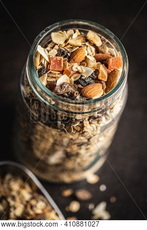 Beakfast cereals in jar. Healthy muesli with oat flakes, nuts and raisins on black table.