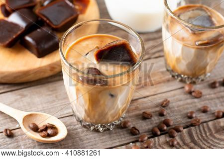 Ice Coffee With Milk Being Poured In A Glass On A Wooden Table