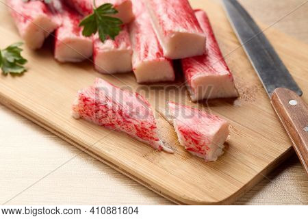 Appetizing crab sticks on wooden cutting board is laying on light table. Selective focus on cut crab stick