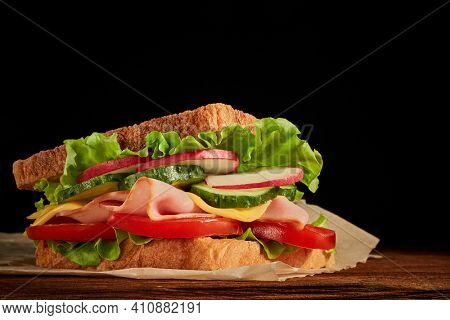 Appetizing sandwich from ham, cheese and vegetables serving on parchment paper is laying on wooden table on black background with copy space.