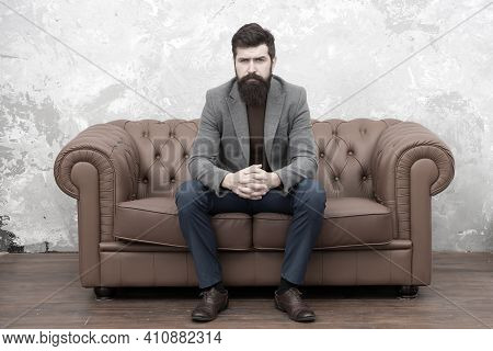 Classy But Casual. Bearded Man Relaxing On Sofa. Man Or Businessman Wearing Informal Suit. Fashion M