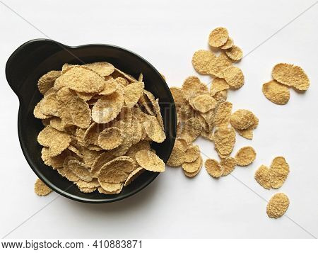 Multi-cereal Flakes In A Black Cup With Scattered Flakes On White Background. Top View.