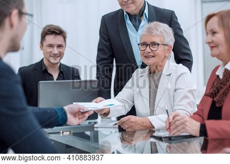 Creative business colleagues discussing diagram around desk in o