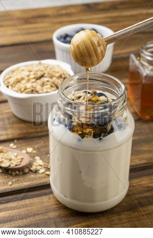 Yogurt, Granola, Bluberry And Honey Over Wooden Table. Wood Utensil Pouring Honey.