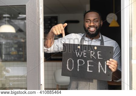 Small Business Concept. Smiling African-american Guy Bakery Stuff In An Apron Points Finger On An Op