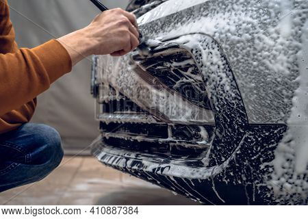 Car Wash Detailing. Worker Cleans Bumper With Auto Shampoo Foam And Brush, Detailed Vehicle Cleaning