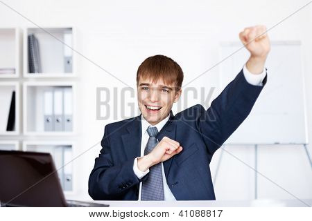 Successful  Businessman Sitting At The Table His Hands In The Air