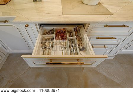 Drawer with silverware and other utensils pulled out with content in cabinet at luxury beige and golden classic kitchen furniture, high angle view