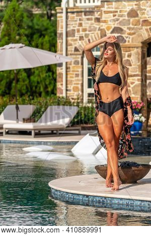 A gorgeous blonde bikini model enjoys a summers day by the pool