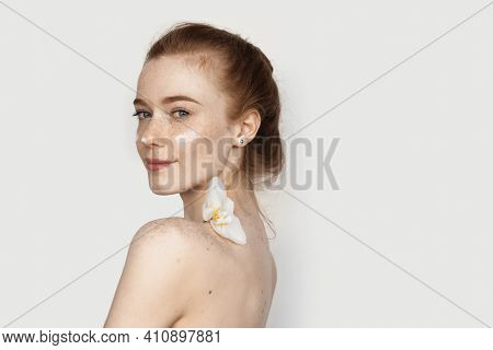 Caucasian Woman With Freckles And Red Hair Is Posing With A Flower On Her Bare Shoulders Applying An