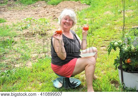 Mature Female Senior Expressions With Her Tomato Plants Outside.