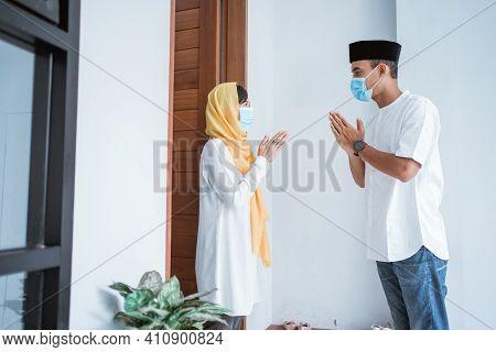 Man And Woman Visiting Home During Eid Mubarak Wearing Medical Mask