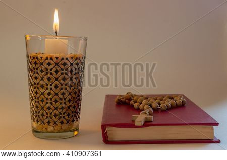 Lighted Candle Standing In Transparent Glass In Dried Peas, Nearby Lying Small Prayer Book With Hard