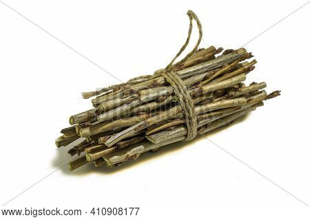 A Bundle Of Twigs Tied With A Hemp Rope On A White Background