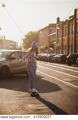 Beautiful Young Skater Woman Riding On Her Longboard In The City Near Cars