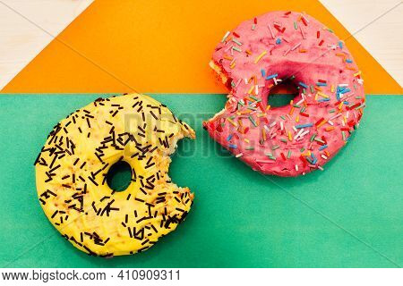 Two Bright Nibbled Doughnuts Lie On A Multicolored Background