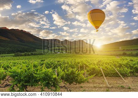 Hot Air Balloon Over The Mountains And Vineyards.