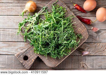 Fresh Green Arugula On A Cutting Board On Wooden Table. Arugula Is Rich In Vitamins And Trace Elemen
