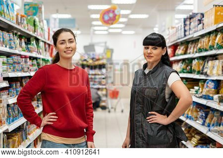 Store Employees, The Director And Manager, Pose Against The Background Of Food Shelves, In The Aisle