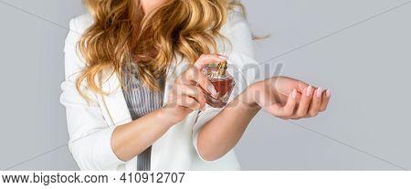 Woman Presents Perfumes Fragrance. Perfume Bottle Woman Spray Aroma. Woman Holding A Perfumes Bottle