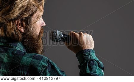 Man Holding A Microphone And Singing. Bearded Man Singing With Microphone. Male Singing With A Micro