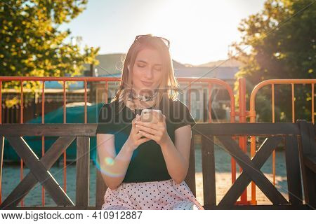 Portrait Of A Woman Sitting On A Park Bench And Communicating On Social Networks. Summer. The Concep