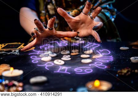 The Female Hands Of The Soothsayer Read The Runes. The Zodiac Circle Glows Above The Runes. The Conc