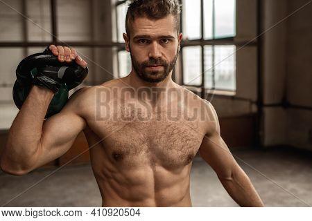 Confident Brutal Bearded Shirtless Man With Muscular Torso Lifting Heavy Kettlebell And Looking At C
