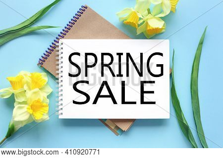Spring Sale. Text On White Notepad Paper On Blue Background. Near Notepad With Yellow Flowers And Gr