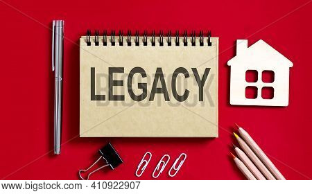 Legacy Text Writtenon Red Background On A Notebook With Pencils And Office Tools And Model Wooden Ho