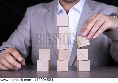 A Businessman Builds A Pyramid Of Ten Wooden Cubes To Write A Word Or Phrase. Copy Space