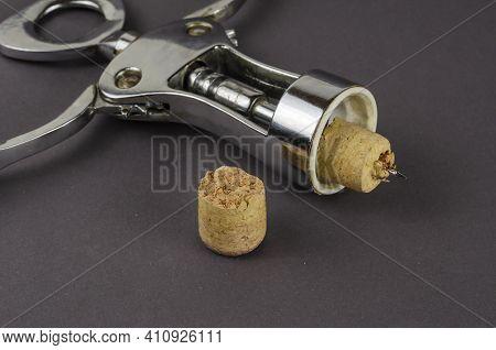 Old Corkscrew And Broken Cork On A Gray Background. The Corkscrew Lies Next To A Broken Wine Cork. S