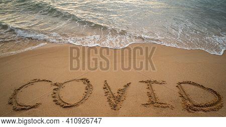 Handwriting Covid On Sand And Foam Wave On Beach. Coronavirus Concept.