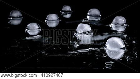 Melting Ice Cubes Are Reflected In A Mirror Surface Against A Dark Background Close-up. Cold Chunks