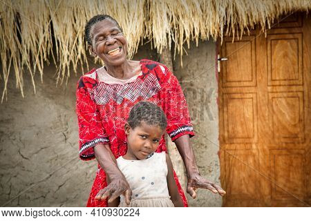 old African woman laughing and her granddaughter standing in her yard in a village in Botswana