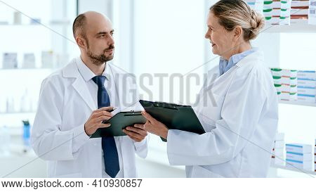Two Apothecary Man And Woman Talking, Discussing Medications.