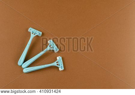 Blue Plastic Razors On A Brown Background. Three New Razor. Top View, Flat Lay. Copy Space