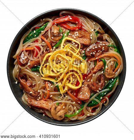 Japchae In Black Bowl Isolated On White. Korean Cuisine Glass Chapchae Noodles Dish With Vegetables